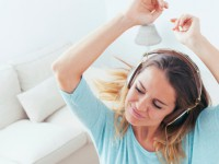 Happy girl dancing at home while listen music with headphones