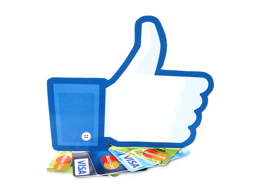 KIEV UKRAINE - MARCH 21 2015: Facebook thumbs up sign printed on paper and placed on cards Visa and MasterCard on white background.New Facebook payment concept.