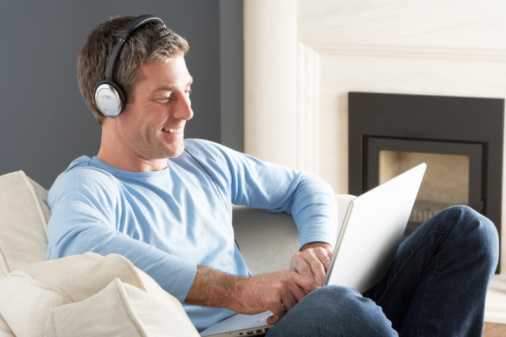 Man Using Laptop Wearing Headphones Relaxing Sitting On Sofa At Home