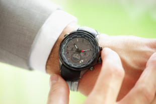 Businessman checking the time on his wrist watch concept for urgency, deadline or running late