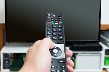 Close up of hand holding and pointing remote control at turned off flat screen television ** Note: Shallow depth of field