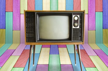 Old vintage TV television on colorful wooden wall background.