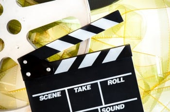 Movie clapper on 35mm yellow unrolled film and cinema reels on neutral background vertical frame
