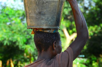 an African woman transports a bucket of water on the head