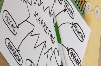 photo showing penl with a printout of a marketing strategy diagram
