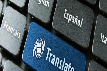 Multilingual translation online concept. Close up of multi language keyboard and translate word key in blue color with clipping path.