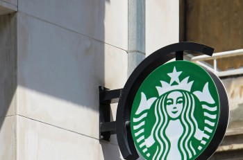 ATHENS GREECE - MAY 03 2015: Starbucks sign outside on building facade wall near coffee shop in Athens. Starbucks is an American global coffee company and coffeehouse chain.