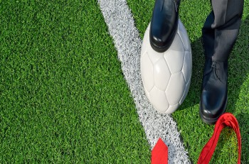 Man in suit, standing on a soccer field, one foot on a soccer ball, his tie to the ground.