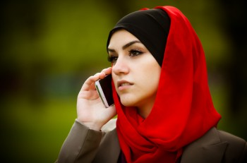 Beautiful muslim woman wearing hijab outdoor portrait. Muslim woman talking on the phone and using technology. Muslim woman is using smart phone ** Note: Soft Focus at 100%, best at smaller sizes