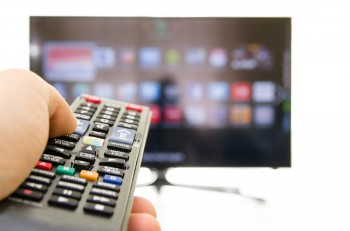Smart tv and hand pressing remote control photo shot