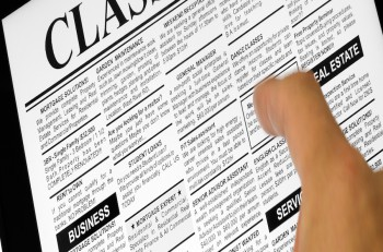 Fake Classified Ad newspaper and Touch Screen business concept.