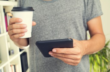 closeup of a young caucasian man wearing a gray t-shirt and with a cup of coffee in his hand uses a tablet computer indoors