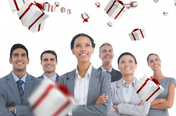 Business people looking up in office against white and red gift box