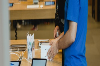 STRASBOURG FRANCE - SEPTEMBER 19 2014: An Apple Inc. genius employee assists a customer with the purchase during the sales launch of the iPhone 6 and iPhone 6 Plus at the company's Place Kleber store in France.
