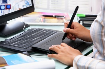 Female graphic designer working in office using tablet pen selective focus