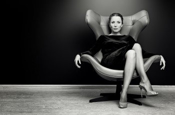 Black-and-white portrait of a stunning fashionable model sitting in a chair in Art Nouveau style. Business, elegant businesswoman. Interior, furniture.