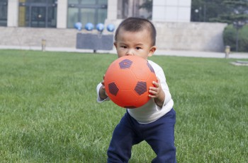 Cute Chinese baby boy playing soccer in meadow shot in Beijing China