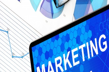 Tablet with marketing plan, graphs and glasses. Marketing concept.