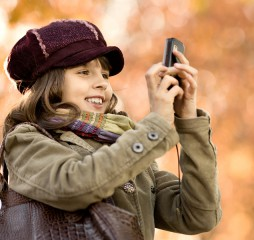 happy beautiful little girl taking a photograph on mobile phone autumnal portrait ** Note: Shallow depth of field