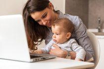Mujer con bebé en la computadora