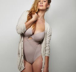 Overweight woman in underwear posing confidently against grey background. Plus size model in body stocking looking at camera.