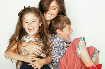 young mother with two children on white, happy smiling family inside