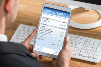 Close-up Of Young Businessperson Online Banking Using Digital Tablet At Computer Desk