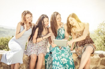 group of girls watching tablet outdoor. concept about technology carefree and people