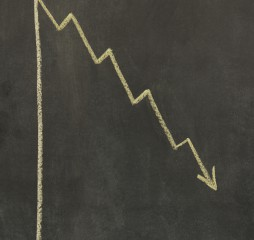 graph drawn on a chalkboard with an arrow showing downward trend
