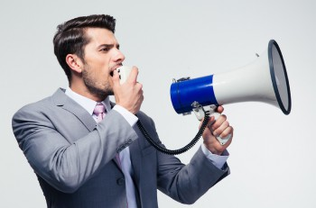 Businessman shouting in megaphone over gray background. Looking