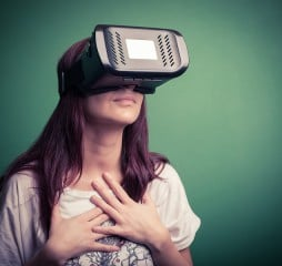 Color shot of a young woman looking through some VR glasses a device with which one can experience virtual reality on a mobile phone.
