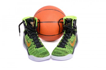 NEW YORK - DEC. 15 2015: A pair of ultra modern Nike Kobe IX Elite Victory high-top green and black flyknit basketball shoes sneakers with a basketball isolated on white