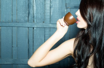 Profile of sensual attractive young woman with long brunette lush hair and bright lips drinking coffee from cup on wooden background horizontal picture