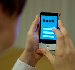Female smartphone user accessing mobile banking system.