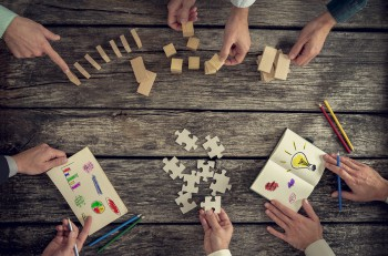 Businesspeople organizing business strategy while holding puzzle pieces writing down ideas on paper and rearranging wooden blocks. Concept of brainstorming management innovation or creativity.