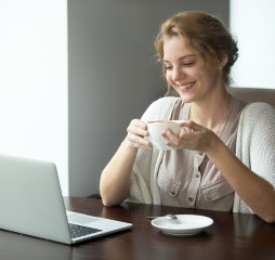 Half-length portrait of young beautiful female working on laptop in coffee shop. Woman sitting with cup of coffee and looking at laptop screen. Attractive model using computer in cafe
