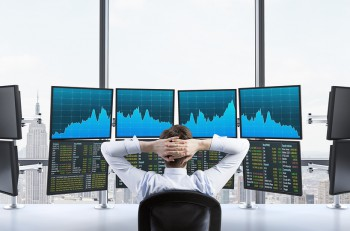 Rear view of a relaxing trader who is sitting in front of a trading station which consists of four screens with financial data. A concept of forex trading. New York panoramic view