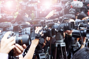press and media camera video photographer on duty in public news event for reporter