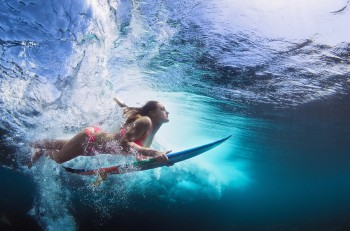 Young girl in bikini - surfer with surf board dive underwater with fun under big ocean wave. Family lifestyle people water sport lessons and beach swimming activity on summer vacation with child