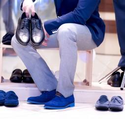 Attractive young man chooses a shoes at a shop.