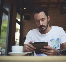 Young businessman reading electronic book on digital tablet during work break in coffee shop
