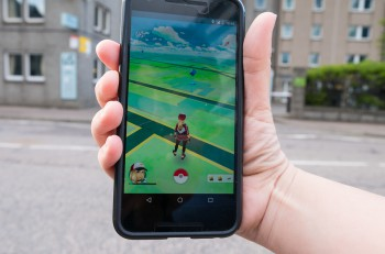 "ABERDEEN UNITED KINGDOM - JULY 15 2016: People playing ""Pokemon GO"" the hit augmented reality smart phone app while trying to find Pokemon on July 15 2016 in Aberdeen United Kingdom."