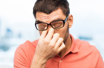 people, eyesight, stress, overwork and business concept - tired man in eyeglasses rubbing his eyes at home or work