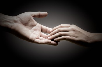 two hands are touching each other over black background concept of solidarity or empathy.