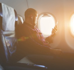 Young hipster guy is enjoying music in headphones via cell telephone and looking at window while is sitting in plane. Businessman is listening audio book via mobile phone during flying in an airplane