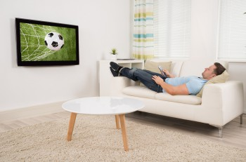 Relaxed Man Watching Football Match At Home