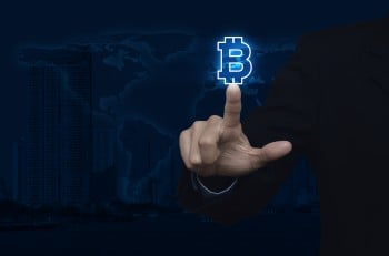 Businessman pressing bitcoin icon over map and city background Choosing bitcoin concept Elements of this image furnished by NASA