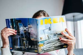 PARIS FRANCE - AUGUST 24 2014: Woman reading IKEA Catalogue before buying furniture for her new house. The catalogue is published annually by the Swedish home furnishing retailer and was first published in Swedish in 1951