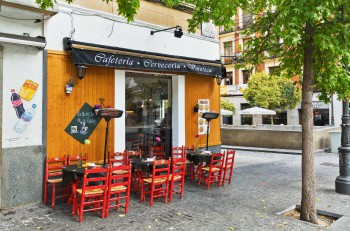 MADRID, SPAIN - OCTOBER 26, 2015 :Traditional small cafe with outdoor seating on one of the main streets of Madrid