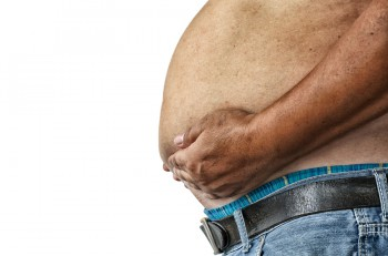 The Dangers of Belly Fat. Obese Man in Jeans Squeeze the Belly Fat. Obese Man is more likely to Clog arteries. Obese Man Have Belly Fat at risk for diabetes. Obese Man Have Belly Fat with diabetes